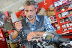 Mechanic working on handlebars scooter. Mechanic working on handlebars of scooter Stock Image