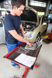 Mechanic working on laptop Stock Photo