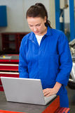 Mechanic working on a laptop Royalty Free Stock Image