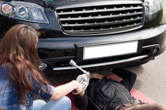 Mechanic working on a roadside breakdown. View over the shoulder of a female driver of a mechanic working on a roadside breakdown as she hands him his tools Stock Photos