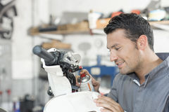 Mechanic working on scooter Stock Photography