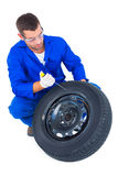 Mechanic working on tire over white background Stock Photo