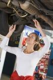 Mechanic working under car Stock Image