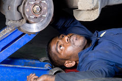 Mechanic working under a car. A mechanic working underneath of a car Stock Image