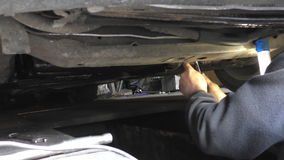 Mechanic working under the car. Car mechanic is fixing faulty part standing underneath vehicle in a workshop repair trench stock footage