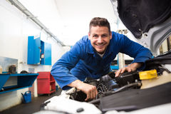 Mechanic working under the hood. At the repair garage royalty free stock image
