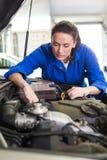 Mechanic working under the hood Royalty Free Stock Image