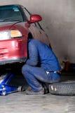 Mechanic working on vehicle. A mechanic working on vehicle front wheel Royalty Free Stock Photography