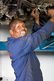Mechanic working on vehicle. From underneath Stock Photos