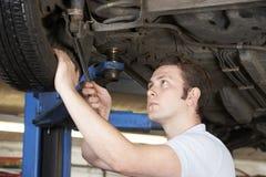 Mechanic Working On Wheel Underneath Car. Male Mechanic Working On Wheel Underneath Car royalty free stock photos