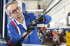 Mechanic working on windshield wipers of car Stock Photography