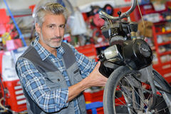 Mechanic workng on motorcycle. Mechanic workng on small motorcycle Royalty Free Stock Photo