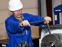 The mechanic on a workplace. Turner is working on the machine. Metal processing.worker works on a lathe Royalty Free Stock Photo