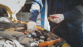 Mechanic works car electrics with voltmeter - electrical wiring. Close up stock photography