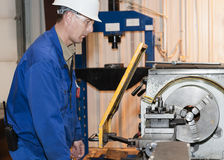 The mechanic works at the lathe. Industrial area. The mechanic works at the lathe royalty free stock images