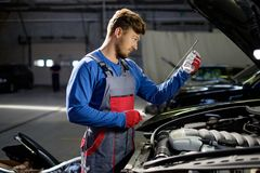 Mechanic in a workshop. Mechanic checking oil level in a car workshop Royalty Free Stock Image