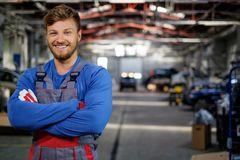 Mechanic in a workshop. Cheerful serviceman in a car workshop Royalty Free Stock Photography