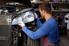 Mechanic in a workshop. Mechanic with new car headlight in a workshop royalty free stock photo