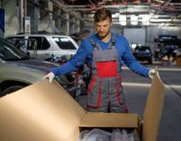 Mechanic in a workshop. Mechanic opening box with new spare parts in a workshop Royalty Free Stock Photography