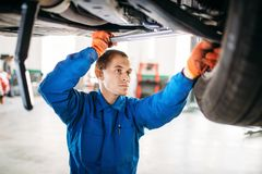 Mechanic repairs the suspension, car on the lift. Mechanic with a wrench repairs the suspension, car on the lift. Tire service, vehicle maintenance royalty free stock image