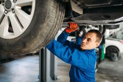 Mechanic repairs the suspension, car on the lift. Mechanic with a wrench repairs the suspension, car on the lift. Tire service, vehicle maintenance stock photos