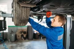 Mechanic repairs the suspension, car on the lift. Mechanic with a wrench repairs the suspension, car on the lift. Tire service, vehicle maintenance stock images