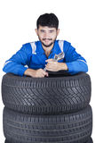 Mechanic with wrench and tires Stock Photography