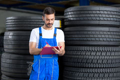 Mechanic writes on clipboard Royalty Free Stock Images