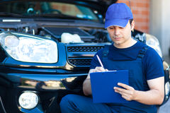 Mechanic writing on clipboard Royalty Free Stock Photography