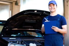 Mechanic writing on clipboard. Car mechanic writing on clipboard royalty free stock images