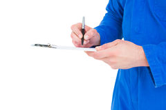 Mechanic writing on clipboard. Male mechanic writing on clipboard over white background Royalty Free Stock Photo
