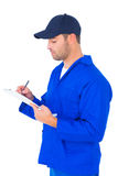 Mechanic writing on clipboard over white background. Male mechanic writing on clipboard over white background Royalty Free Stock Photos