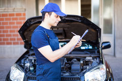 Mechanic writing on a clipboard Royalty Free Stock Photography