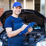 Mechanic writing on a clipboard Royalty Free Stock Photos