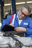Mechanic writing down something on clipboard Royalty Free Stock Photos