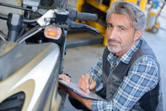 Mechanic writing on form Royalty Free Stock Photography