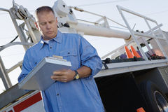 Mechanic Writing Notes On Clipboard Against A Truck Royalty Free Stock Photo