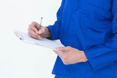 Mechanic writing notes on clipboard. Cropped image of mechanic writing notes on clipboard over white background Stock Image