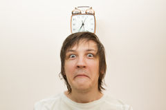 Mechanical alarm clock  stand on head funny white man Stock Photography