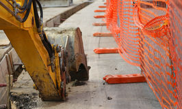 Mechanical arm of the excavator digging on the road Royalty Free Stock Photo