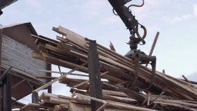 Mechanical arm loader unloads lumber scraps from heavy truck at sawmill factory. Cold cloudy winter day stock footage