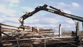 Mechanical arm loader unloads timber scraps from heavy truck at sawmill facility. Cold cloudy winter day stock video