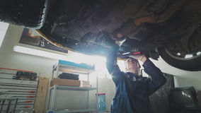 Mechanical auto workshop - a mechanic checks the suspension of car, wide angle stock photos