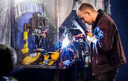 Mechanical carefully welding the tube Royalty Free Stock Photography