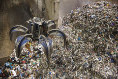 Mechanical claw hand grabbing pile of mixed waste Stock Images