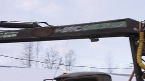Mechanical claw loader unloads lumber scraps from heavy truck at sawmill factory. Cold cloudy winter day stock footage