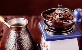Mechanical coffee grinder, old copper cezve and coffee beans. Over wooden table as background. Stock Image