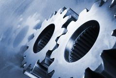 Mechanical composition in blue. Large gears lying on blue brushed aluminum Royalty Free Stock Photos
