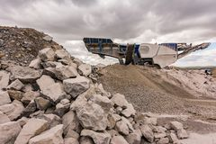 Mechanical conveyor belt to pulverize rock and stone and generate grave. L stock images