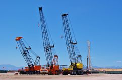 Mechanical Cranes in the desert. Three mechanical Cranes Parked in the Desert royalty free stock images